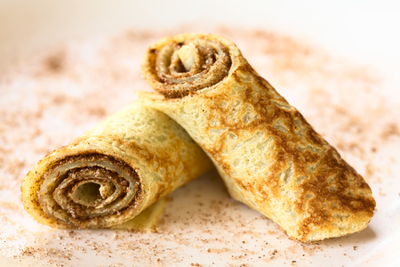 filled roll: Crepe rolls filled with cinnamon and sugar, photographed with natural light (Selective Focus, Focus on the front side of the right roll)