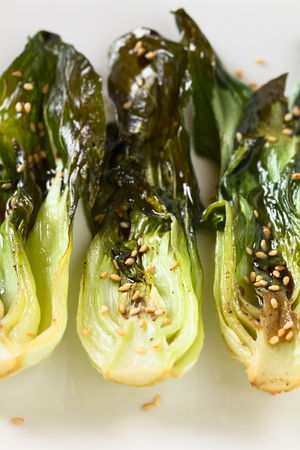 bok choy: Baked bok choy or pak choi seasoned with soy sauce and roasted sesame seeds, photographed with natural light (Selective Focus, Focus one third into the bok choy in the middle)