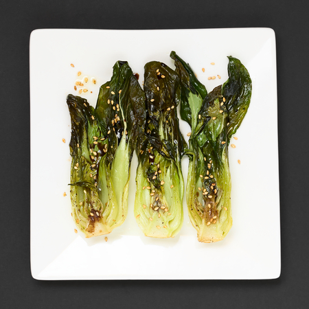 bok choy: Baked bok choy or pak choi seasoned with soy sauce and roasted sesame seeds, photographed overhead with natural light