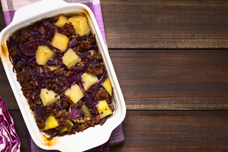 mincemeat: Baked red cabbage, apple, mincemeat and potato casserole in dish, photographed overhead on dark wood with natural light (Selective Focus, Focus on the top of the dish) Stock Photo
