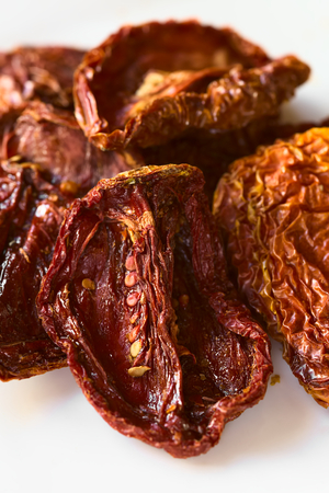 sundried: Sun-dried tomato halves on white plate, photographed with natural light (Selective Focus, Focus in the middle of the image) Stock Photo