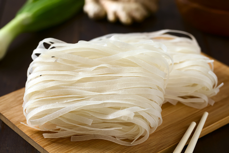 Raw rice flour noodles on wooden board, photographed with natural light (Selective Focus, Focus in the middle of the noodles)