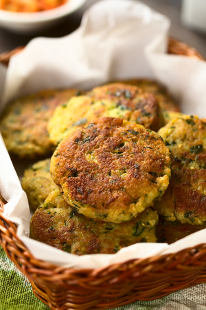 Zucchini, couscous and parsley fritters in basket, photographed with natural light (Selective Focus, Focus in the middle of the top fritter) Stock Photo
