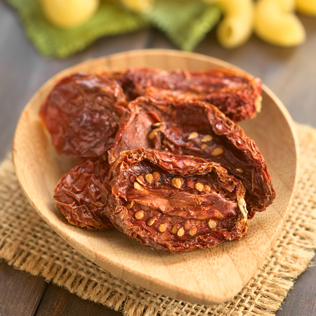 sundried: Sun-dried tomato halves on bamboo plate, photographed with natural light (Selective Focus, Focus in the middle of the first tomato half)