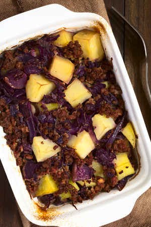 mincemeat: Baked red cabbage, apple, mincemeat and potato casserole in dish, photographed overhead with natural light (Selective Focus, Focus on the top of the dish)