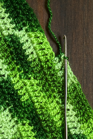 Crochet handicraft, making a place mat out of green yarn with a pattern of double stitches using a metal crochet hook or needle, photographed overhead with natural light