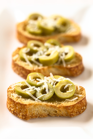 hard cheese: Crostini with green olive slices and freshly grated parmesan-like hard cheese, photographed with natural light (Selective Focus, Focus in the middle of the first crostini) Stock Photo
