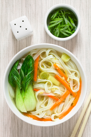 asian natural: Vegetarian Asian rice noodle soup with bok choy, carrots and spring onion, photographed overhead with natural light (Selective Focus, Focus on the top of the soup)