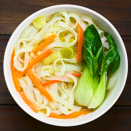 noodle soup: Vegetarian Asian rice noodle soup with bok choy, carrots and spring onion, photographed overhead with natural light Stock Photo