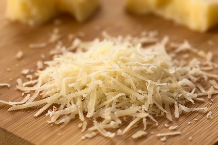 hard cheese: Freshly grated parmesan-like hard cheese on wooden board with cheese pieces in the back, photographed with natural light (Selective Focus, Focus one third into the grated cheese) Stock Photo