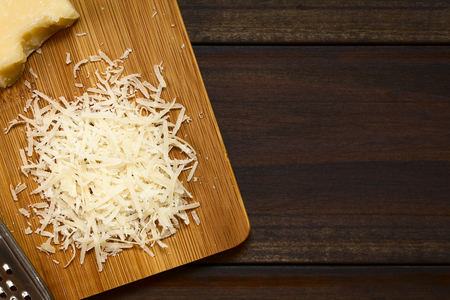 hard cheese: Freshly grated parmesan-like hard cheese on wooden board, photographed overhead on dark wood with natural light (Selective Focus, Focus on the grated cheese)