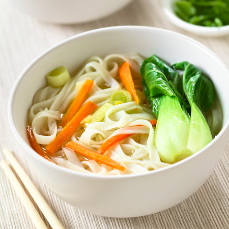 quadratic: Vegetarian Asian rice noodle soup with bok choy, carrots and spring onion, photographed with natural light (Selective Focus, Focus in the middle of the soup)