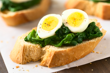 hard boiled: Crostini roasted bread slices with cooked spinach leaves and hard boiled quail eggs seasoned with black pepper, photographed with natural light (Selective Focus, Focus on the front of the egg yolks) Stock Photo