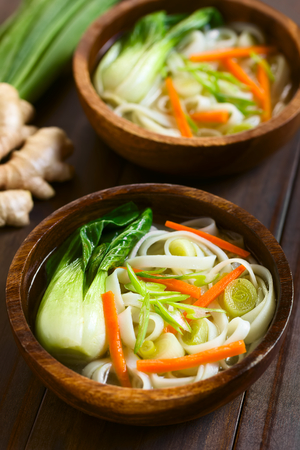asian natural: Vegetarian Asian rice noodle soup with bok choy, carrots and spring onion, photographed with natural light (Selective Focus, Focus in the middle of the first soup)