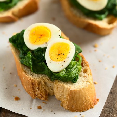 quadratic: Crostini roasted bread slices with cooked spinach leaves and hard boiled quail eggs seasoned with black pepper, photographed with natural light (Selective Focus, Focus on the front of the first egg yolk)