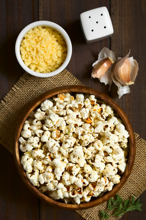 Homemade fresh savory popcorn with cheese, garlic and dried oregano in wooden bowl, photographed overhead on dark wood with natural light (Selective Focus, Focus on the top of the popcorn)