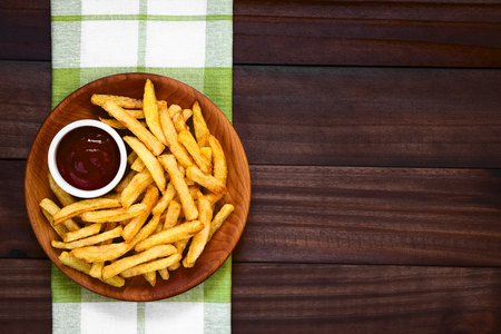Fresh homemade crispy French fries with a small bowl of ketchup on wooden plate, photographed overhead on dark wood with natural light