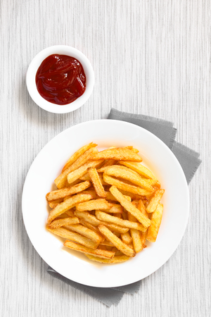 fried food: Fresh homemade crispy French fries on plate with a small bowl of ketchup on the side, photographed overhead with natural light Stock Photo