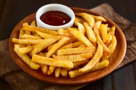 frites: Fresh homemade crispy French fries with a small bowl of ketchup on wooden plate, photographed with natural light (Selective Focus, Focus one third into the fries)