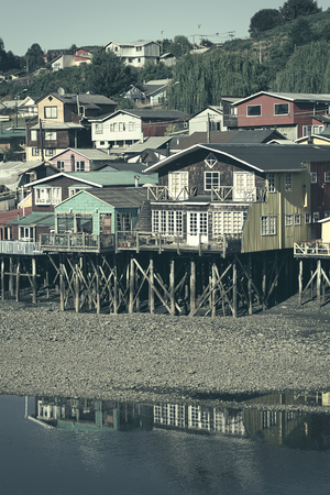 pile dwelling: Colorful Palafitos, traditional wooden stilt houses at low tide in Castro, the capital of the Chiloe Archipelago in Chile (Digitally Altered: Toned Image) Stock Photo