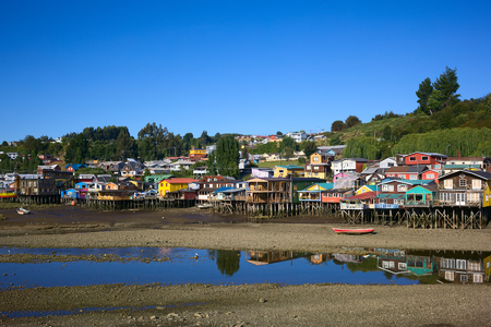 pile dwelling: Colorful Palafitos, traditional wooden stilt houses at low tide in Castro, the capital of the Chiloe Archipelago in Chile Stock Photo