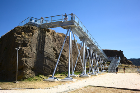 pedestrian bridges: NIEBLA, CHILE - FEBRUARY 2, 2016: Unidentified people walking on the metal pathway leading through the ruins of the fort of Niebla, Chile on February 2, 2016. The fort, located at the mouth of the Valdivia river, is part of the Valdivian fort system and w