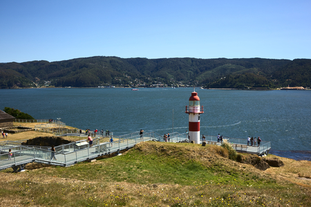 declared: NIEBLA, CHILE - FEBRUARY 2, 2016: Lighthouse of the Niebla fort, Chile on February 2, 2016. The fort, located at the mouth of the Valdivia river, is part of the Valdivian fort system and was declared national monument in 1950. The metal pathway was made t Editorial
