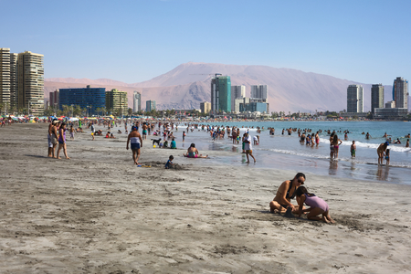 water town: IQUIQUE, CHILE - JANUARY 23, 2015: Unidentified people enjoying the water and playing in the sand on the crowded Cavancha beach on January 23, 2015 in Iquique, Chile. Iquique is a popular beach town and free port city in Northern Chile.
