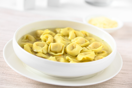 Traditional Italian Tortellini in Brodo (broth) soup, photographed with natural light (Selective Focus, Focus in the middle of the image) Stock Photo