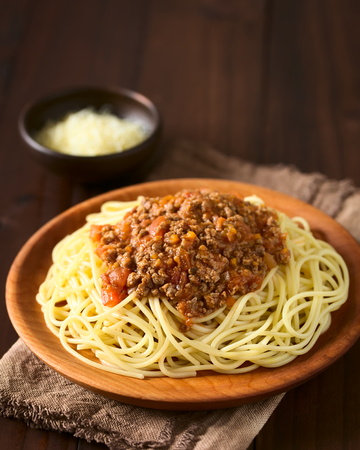 mincemeat: Spaghetti with homemade bolognese sauce made of fresh tomato, mincemeat, onion, garlic and carrot, served on wooden plate with grated cheese in the back, photographed with natural light (Selective Focus, Focus on the front of the sauce)