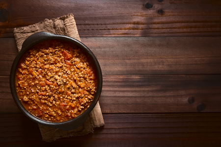 Homemade bolognese sauce made of fresh tomatoes, onion, carrot, garlic and mincemeat served in rustic bowl, photographed overhead on dark wood with natural light Stock Photo