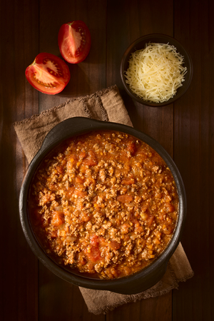 Homemade bolognese sauce made of fresh tomatoes, onion, carrot, garlic and mincemeat, served in rustic bowl, photographed overhead on dark wood with natural light (Selective Focus, Focus on the top of the sauce) Standard-Bild
