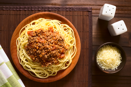 mincemeat: Spaghetti with homemade bolognese sauce made of fresh tomato, mincemeat, onion, garlic and carrot, served on wooden plate with grated cheese on the side, photographed overhead with natural light (Selective Focus, Focus on the sauce) Stock Photo