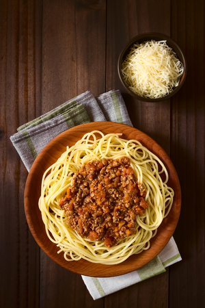 mincemeat: Spaghetti with homemade bolognese sauce made of fresh tomato, mincemeat, onion, garlic and carrot, served on wooden plate with grated cheese on the side, photographed overhead with natural light
