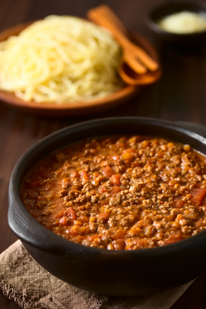 mincemeat: Homemade bolognese sauce made of fresh tomatoes, onion, carrot, garlic and mincemeat, served in rustic bowl with cooked spaghetti and grated cheese in the back, photographed on dark wood with natural light (Selective Focus, Focus in the middle of the sauc