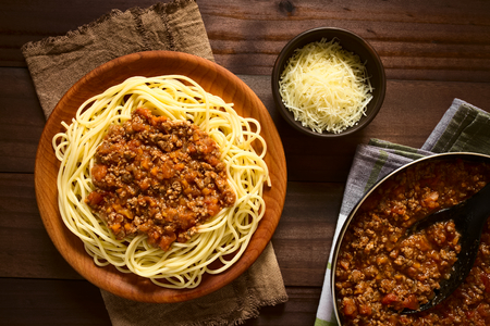 Spaghetti with homemade bolognese sauce made of fresh tomato, mincemeat, onion, garlic and carrot, served on wooden plate with grated cheese and skillet with sauce on the side, photographed overhead with natural light Stock Photo