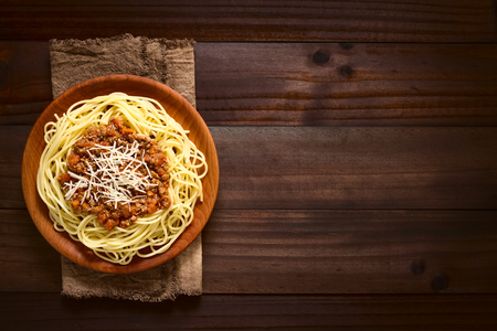 mincemeat: Spaghetti with homemade bolognese sauce made of fresh tomato, mincemeat, onion, garlic and carrot, served on wooden plate with grated cheese on top, photographed overhead on dark wood with natural light