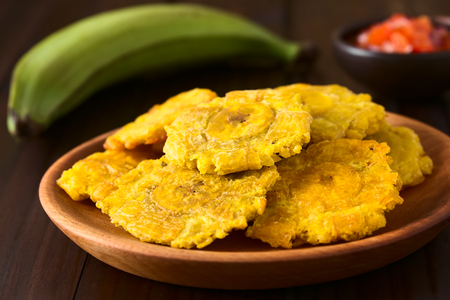 Patacon or toston, fried and flattened pieces of green plantains, a traditional snack or accompaniment in the Caribbean, photographed on dark wood with natural light (Selective Focus, Focus on the front of the top patacon)