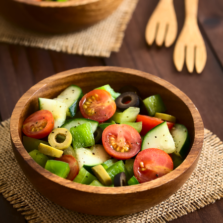quadratic: Fresh salad of black and green olives, cherry tomatoes, green bell pepper and cucumber, seasoned with salt, pepper, dried oregano and basil, served in wooden bowl, photographed on dark wood with natural light (Selective Focus, Focus in the middle of the s