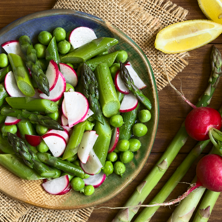 plato de ensalada: Fresh green asparagus, radish and pea salad served on plate, ingredients on the side, photographed overhead with natural light   Foto de archivo