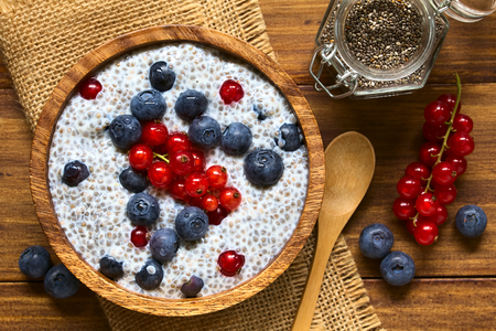 Chia (lat. Salvia hispanica) seed pudding with blueberries and redcurrants in wooden bowl, photographed overhead on wood with natural light (Selective Focus, Focus on the top of the pudding)