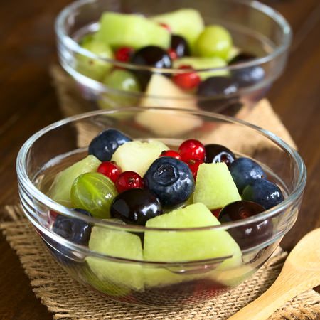 quadratic: Fresh fruit salad made of cantaloupe melon, blueberry, redcurrant, gooseberry and sweet cherry in glass bowls, photographed on dark wood with natural light (Selective Focus, Focus in the middle of the first salad) Stock Photo