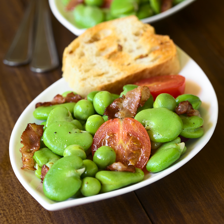 Broad bean, green pea, cherry tomato and fried bacon salad with toasted bread, photographed on dark wood with natural light (Selective Focus, Focus one third into the salad) Stock Photo