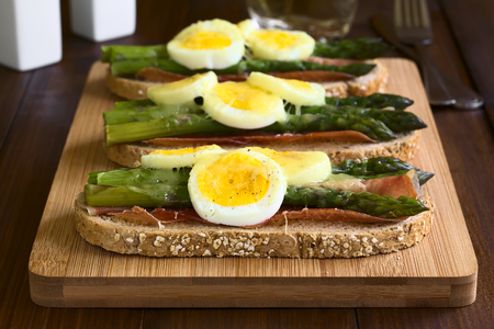Baked green asparagus, ham, hard-boiled egg and grated cheese warm sandwich on wooden board, photographed on dark wood with natural light (Selective Focus, Focus on the front of the first sandwich)