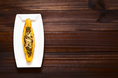 mincemeat: Baked ripe plantain stuffed with mincemeat, olive, green bell pepper and onion, sprinkled with cheese, a traditional dish in Central America called Canoa de Platano (Plantain Canoe), photographed overhead on dark wood with natural light Stock Photo