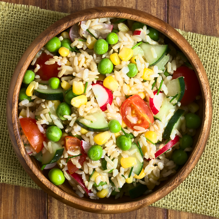 quadratic: Brown rice salad with cherry tomato, corn, cucumber, radish, pea and chives served in bowl, photographed overhead on dark wood with natural light (Selective Focus, Focus on the top of the salad)