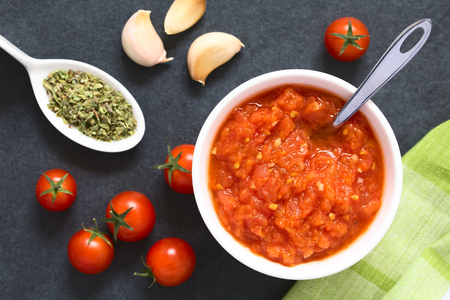 Homemade traditional Italian marinara or pomodoro tomato sauce made of fresh tomato, garlic, dried oregano and salt, served in bowl with ingredients on the side, photographed overhead on slate with natural light (Selective Focus, Focus on the top of the s