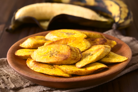 Fried slices of ripe plantains, a traditional and popular snack and accompaniment in Central America and Northern South America, photographed with natural light (Selective Focus, Focus on the front of the top slice)