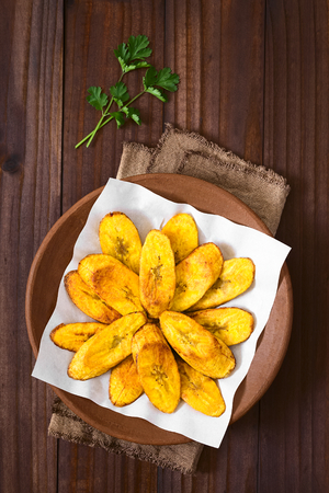 creole: Fried slices of ripe plantains, a traditional and popular snack and accompaniment in Central America and Northern South America, photographed overhead on dark wood with natural light Stock Photo
