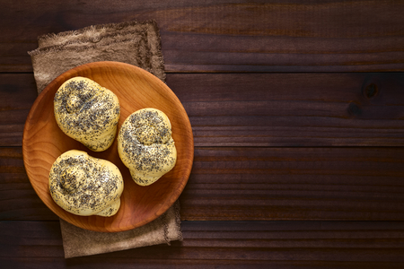 Homemade poppy seed bread rolls on wooden plate, photographed overhead on dark wood with natural light Stock Photo